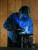 stock photo of blue-collar-worker  - Metal worker welds two pieces of metal together - JPG