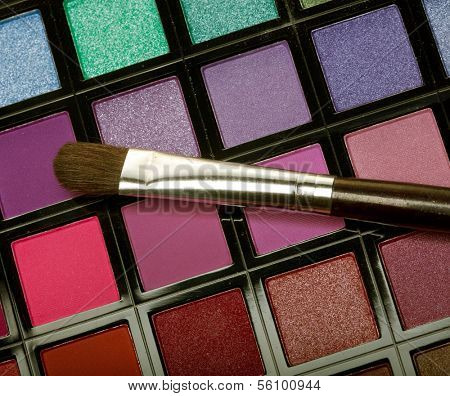 multicolored eye shadows with cosmetics brush