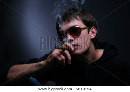 Dark Portrait Of A Smoking Man In Sunglasses