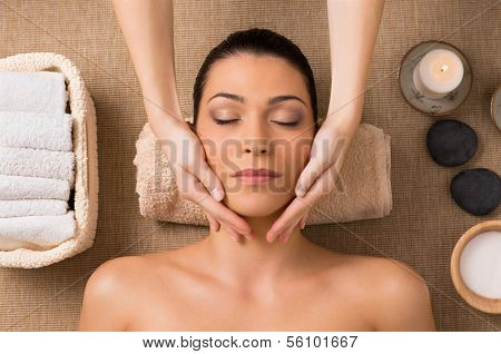 Beautiful Latin Woman Getting Facial Massage At Spa