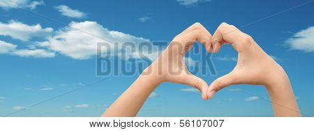 Concept or conceptual human male or man and woman hands in love, Valentines shape or symbol of heart over blue sky background