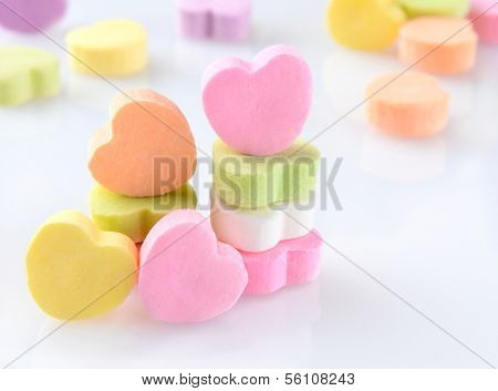 Closeup of candy Valentines hearts on a white reflective surface. Horizontal format with out of focus candies in the background.