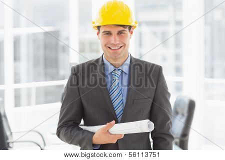Happy architect holding blueprints smiling at camera in the office
