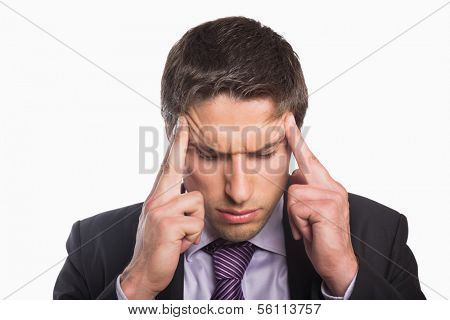 Close-up of a young tensed businessman suffering from headache against white background