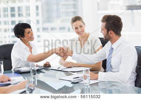 Side view of executives shaking hands after a business meeting in the office