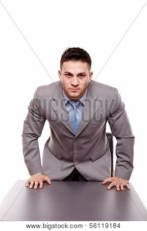 Menacing Businessman With Hands On The Desk