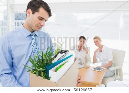 Young businessman leaving office with his belongings and colleagues in background