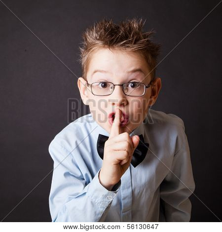 Little boy making sign to keep silence