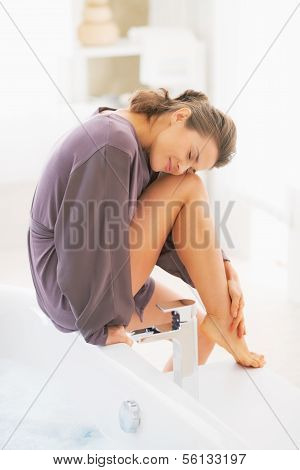 Relaxed Young Woman Sitting In Bathroom