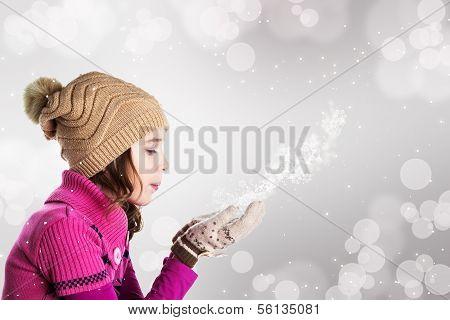 glücklich schöne Mädchen bläst Schneeflocken