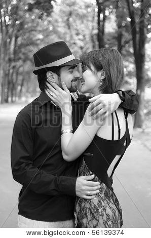 Romantic couple kisses in a park
