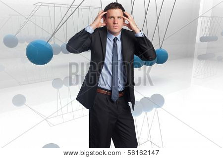 Stressed businessman with hands on head against blue newtons cradle