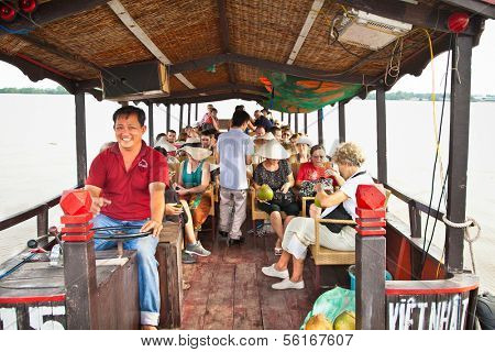 MEKONG, VIETNAM-NOV 18, 2013: Tourists traveling through the channels of the Mekong delta on Nov 18, 2013. Vietnam. Mekong Delta is home of people who live along the many channels.