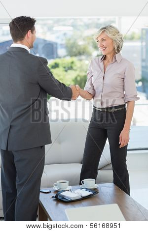 Side view of two executives shaking hands over a coffee table in living room at home