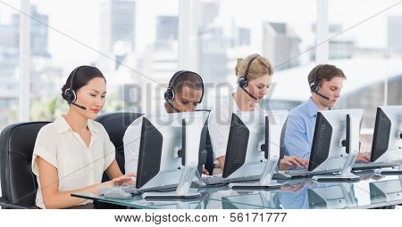 Group of business colleagues with headsets using computers at office desk
