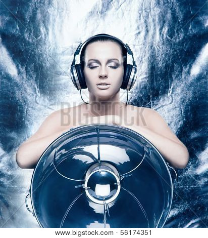 Glamour and bizarre portrait of young and beautiful woman listening to the music over creative winter background