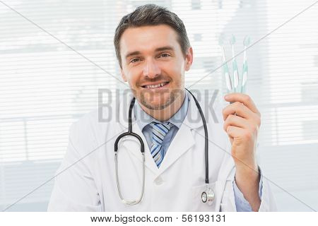 Portrait of a smiling doctor holding toothbrushes in his office