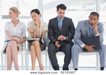 Four business people waiting for job interview in a bright office
