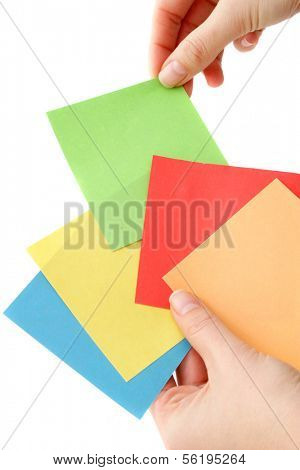 A human hand picks a colored note. All isolated on white background