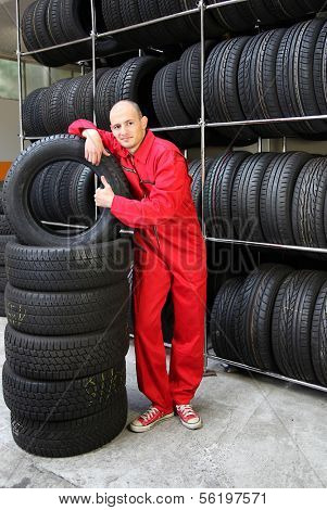 A motivated worker in a tire workshop making a positive gesture.