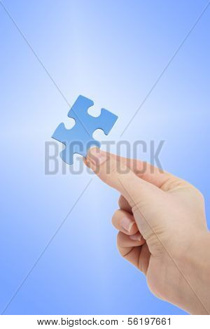 A person holding a blue piece of a puzzle in his hand in front of a white to blue gradient