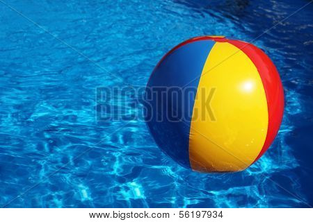 An inflatable colored plastic ball swimming in a shiny blue swimming pool.