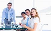 image of half-dressed  - Smartly dressed young executives around conference table in office - JPG