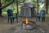 stock photo of canopy  - Pitched tent crackling campfire two chairs and metal roasting sticks - JPG