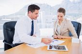 picture of half-dressed  - Smartly dressed young man and woman in a business meeting at office desk - JPG