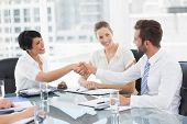 stock photo of half-dressed  - Side view of executives shaking hands after a business meeting in the office - JPG