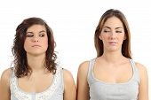image of annoying  - Two girls looking each other angry isolated on a white background - JPG