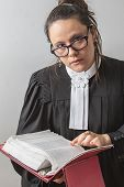 stock photo of toga  - thirty something brunette woman wearing a canadian lawyer toga with a red criminal law book in hand looking over her glasses - JPG