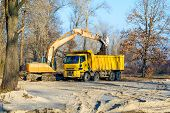 stock photo of excavator  - An orange excavator and a yellow truck working in the park under a cold morning sunlight in winter - JPG