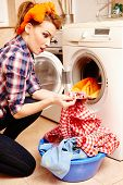 stock photo of dirty-laundry  - Portrait of surprised housewife spotting a stain on the laundry - JPG