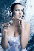 stock photo of e-cigarettes  - Glamour and bizarre portrait of young and beautiful woman smoking the electronic cigarette and listening to the music over creative winter background - JPG