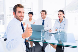 foto of half-dressed  - Portrait of an executive gesturing thumbs up with recruiters during a job interview at office - JPG