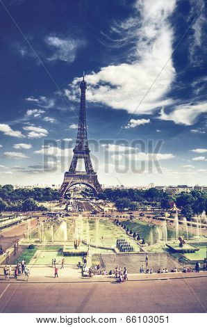 Toned faded view of the Eiffel Tower, Paris looking across the park and fountains with pedestrians and tourists on a sunny day with a cloudy blue sky