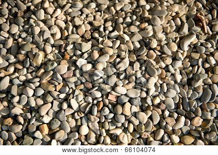 Background of smooth waterworn pebbles in different colors and sizes on a beach or riverbed eroded by the action of the water