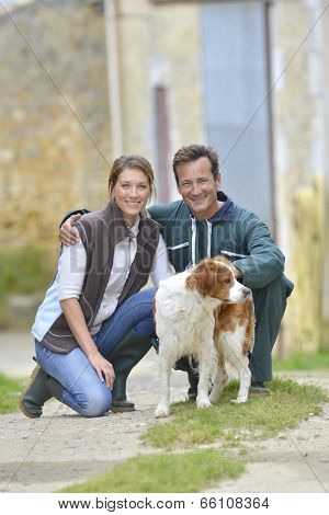 Couple of farmers with dogs around farm house