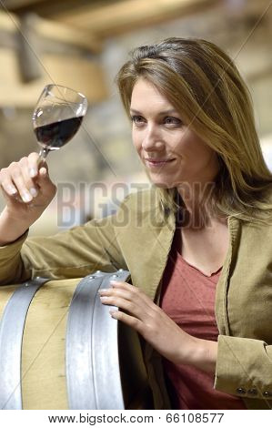 Woman tasting red wine in cellar