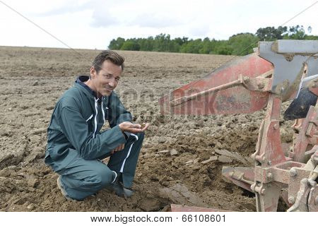 Farmer checking on cultivated ground quality