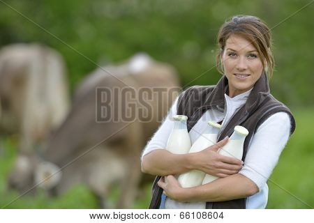 Smiling breeder woman holding bottles of milk