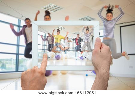 Hand holding tablet pc showing fit people jumping in bright exercise room