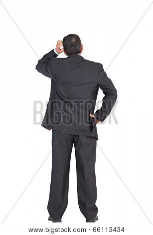 Mature businessman standing and scratching head on white background
