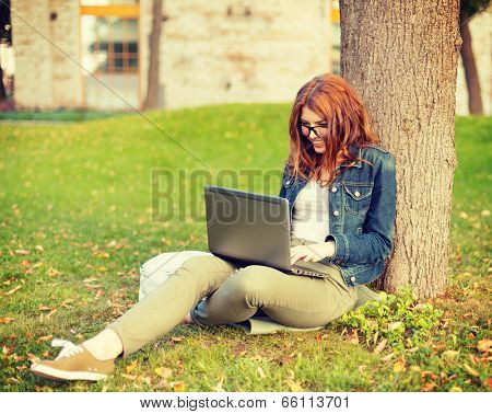 education, technology and internet concept - smiling redhead teenager in eyeglasses with laptop computer