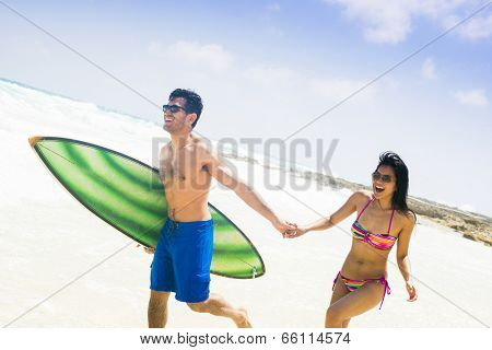Young sexy couple at the beach, running with a surf board in a summer day