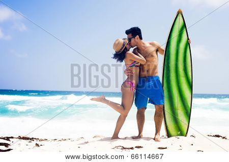 Young sexy couple kissing at the beach, ready to surf in a summer day