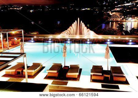 Swimming Pool With Fountain In Night Illumination At The Luxury Hotel, Crete Island, Greece