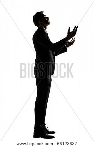 Silhouette of Asian businessman praying, full length portrait isolated on white background.
