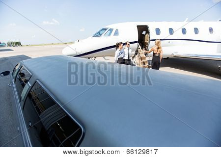 Woman boarding private jet with limousine in foreground at airport terminal